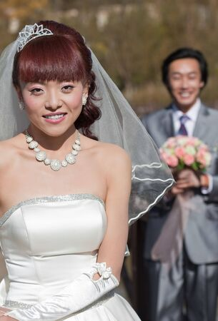 smiling bride with groom in background (2) photo
