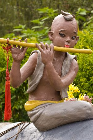 statue of asian boy with flute photo