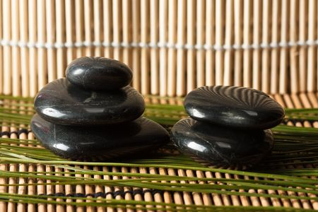 thermotherapy: detail of volcanic hot-stones for thermo-therapy on bamboo mat