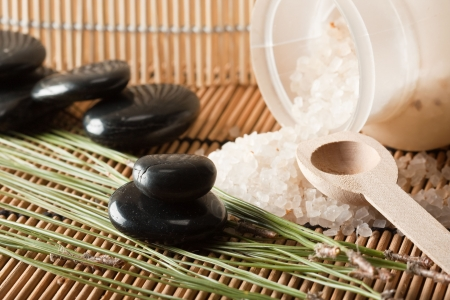 volcanic stones: detail of aromatic salt for spa treatment and basalt stones on bamboo mats (1)