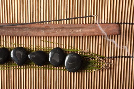 thermotherapy: burning incense and volcanic hot-stones placed on bamboo mat Stock Photo