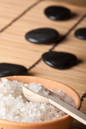 thermotherapy: aromatic salt in stone bowl with volcanic hot-stones on bamboo mat in background