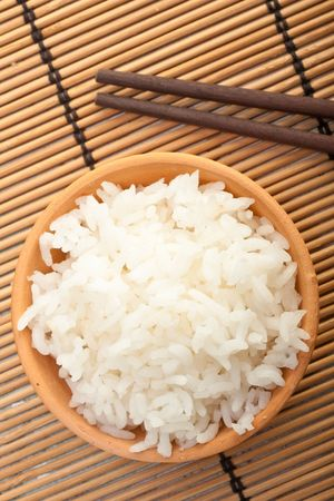 Rice bowl and chopsticks on bamboo mat