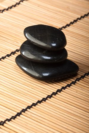 thermotherapy: pile of black basalt stones for thermotherapy on bamboo mat (2)