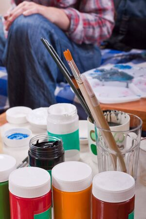 Jars of colorful paint, brushes, palette used for body painting photo