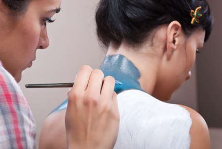 MUA painting background layers on girls back (blue and white) photo