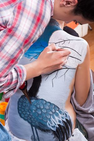 makeup artist body-painting a crane on girls back photo