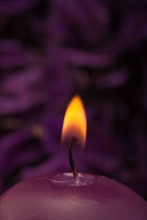 closeup of burning candle with soothing purple background Stock Photo