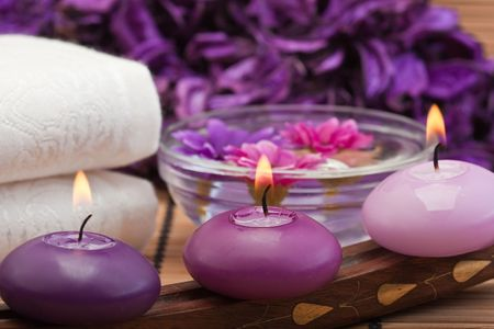 three purple toned candles and flowers in spa setting (1) Stock Photo