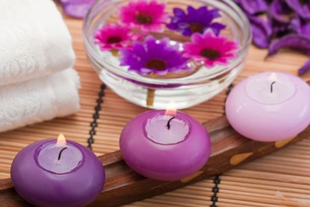 three purple toned candles and flowers in spa setting (2) photo