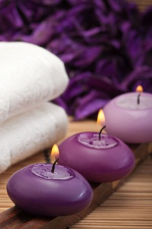 purple candles with white towel in spa setting (1) photo