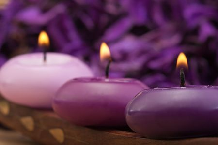 cosy: three burning purple toned candles with purple background
