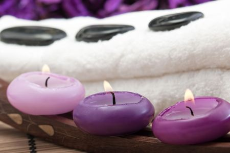 volcanic stones: black hotstones on white towel with purple candles (2)