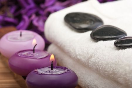 thermotherapy: black hotstones on white towel with purple candles (1)