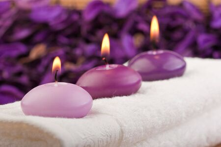 zen candles: three purple toned candles on white massage towel (1) Stock Photo