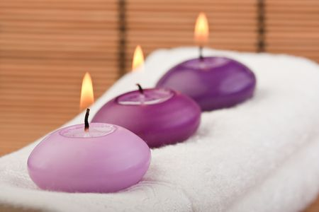 purple toned candles on white towel and bamboo background (2)