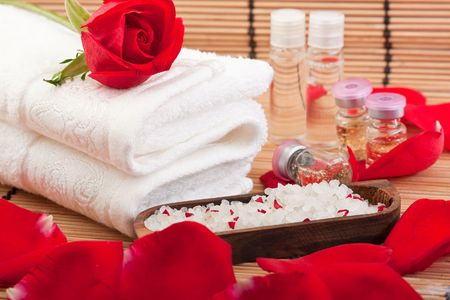 swedish: roses, rose petals, rose extract bottles, bathing salt and a towel Stock Photo