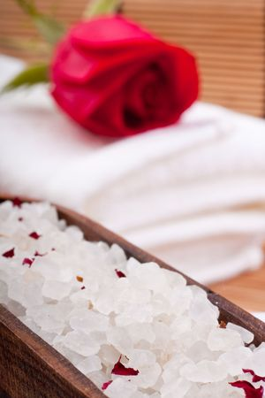 aromatic rose bathing salt with rose on white towel photo