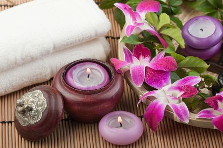 orchids, candles and a towel on bamboo mat (1) photo