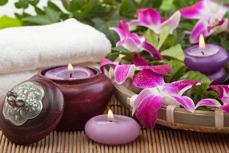 white candle: orchids, candles and a towel on bamboo mat (2) Stock Photo