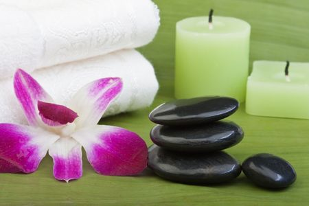 black stones for thermo-therapy with orchids and towel on banana leaves (1) photo