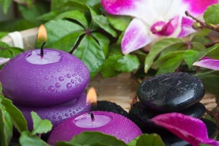 wet purple toned candles and hotstones in tropical setting (2) Stock Photo