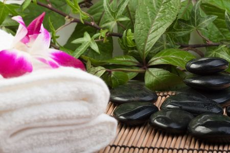thermotherapy: white towel, orchid and hotstones in tropical setting
