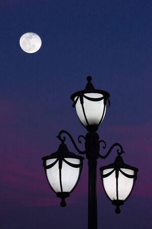classic street lantern with colorful sky and moon at dusk photo