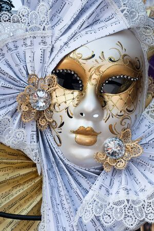 yellow and white venice carnival mask photo
