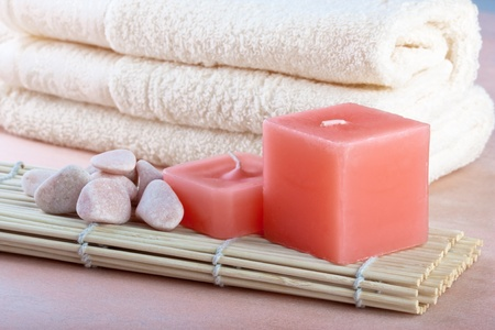 red candles and towel with peach background photo