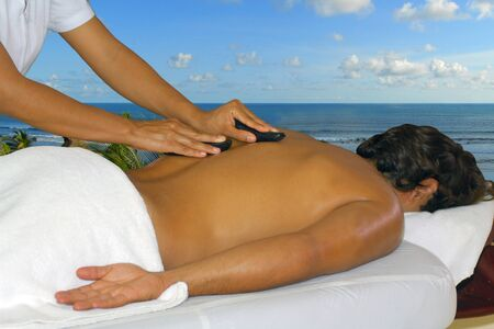 Portrait of a young man laying down enjoying a hot stone back massage at a beauty spa near the beach