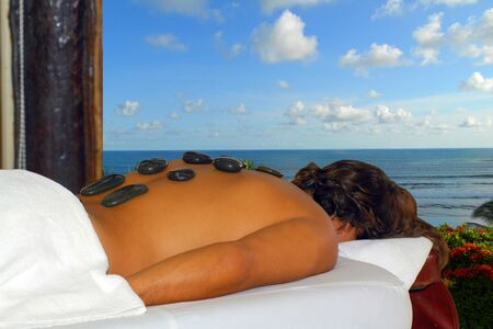 Portrait of a young man laying down relaxing after enjoying a hot stone back massage at a beauty spa near the beach