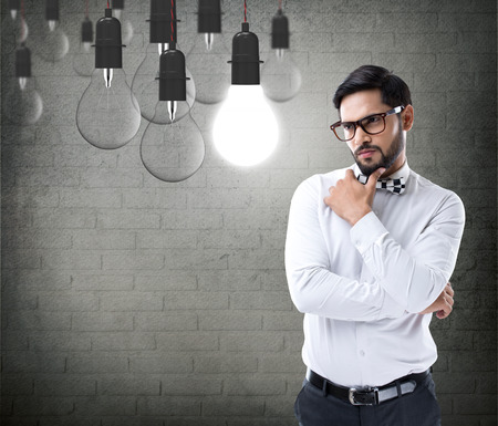 Thoughtful businessman looking at light bulb