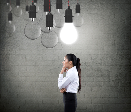 to contemplate: Businesswoman with glowing light bulb Stock Photo