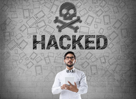 to warn: Businessman using digital tablet in front of hacked symbol Stock Photo