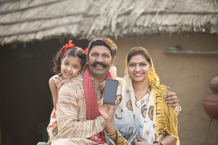 Delighted rural family holding new mobile phone