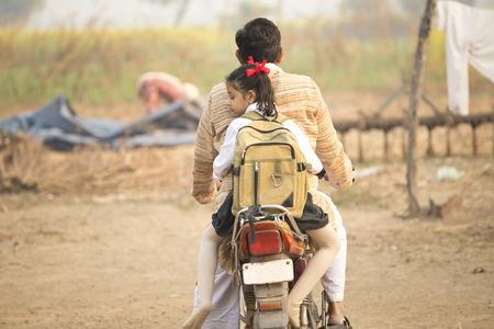 Father and schoolgirl riding motorbike in village