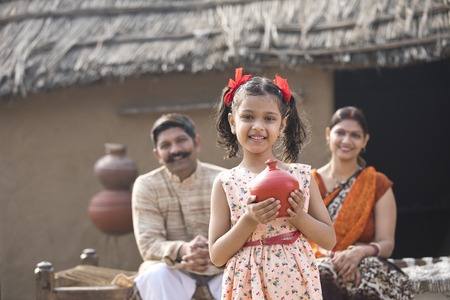 Indian little girl holding piggy bank in front of parents