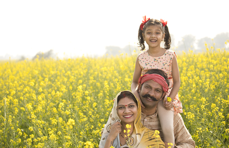 Portrait of happy rural family in rapeseed agricultural field