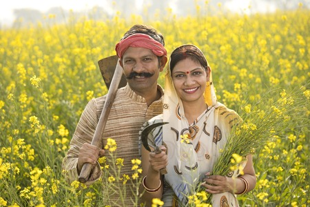 Rural Indian couple farming in agricultural field Imagens