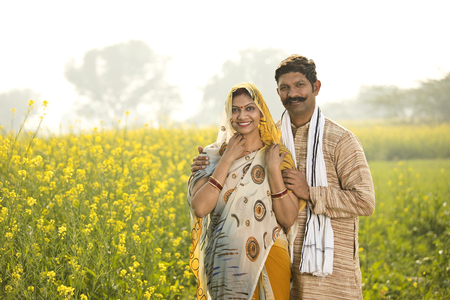 Rural couple standing in rapeseed field