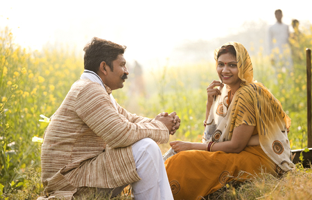 Rural Indian couple relaxing in agricultural field