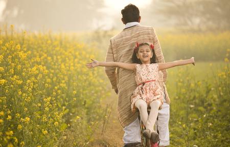 Vater mit Tochter, die Fahrrad auf Landwirtschaftsfeld fährt