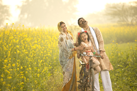 Rural Indian family with bicycle in agricultural field