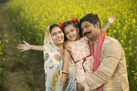 Rural happy Indian family in agricultural field