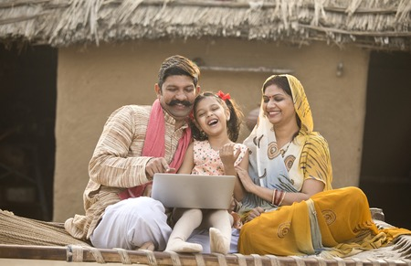Rural Indian family using laptop on traditional bed at village Stockfoto