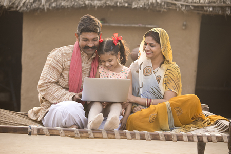 Rural Indian family using laptop on traditional bed at village Imagens