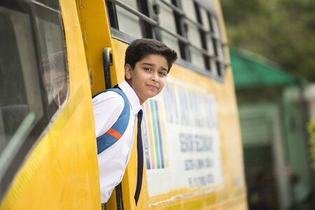 Indian schoolboy getting into the school bus