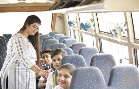 Teacher taking care of children while traveling in school bus
