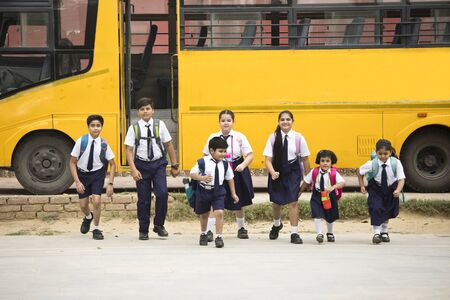 Schoolboys and schoolgirls walking of the school bus